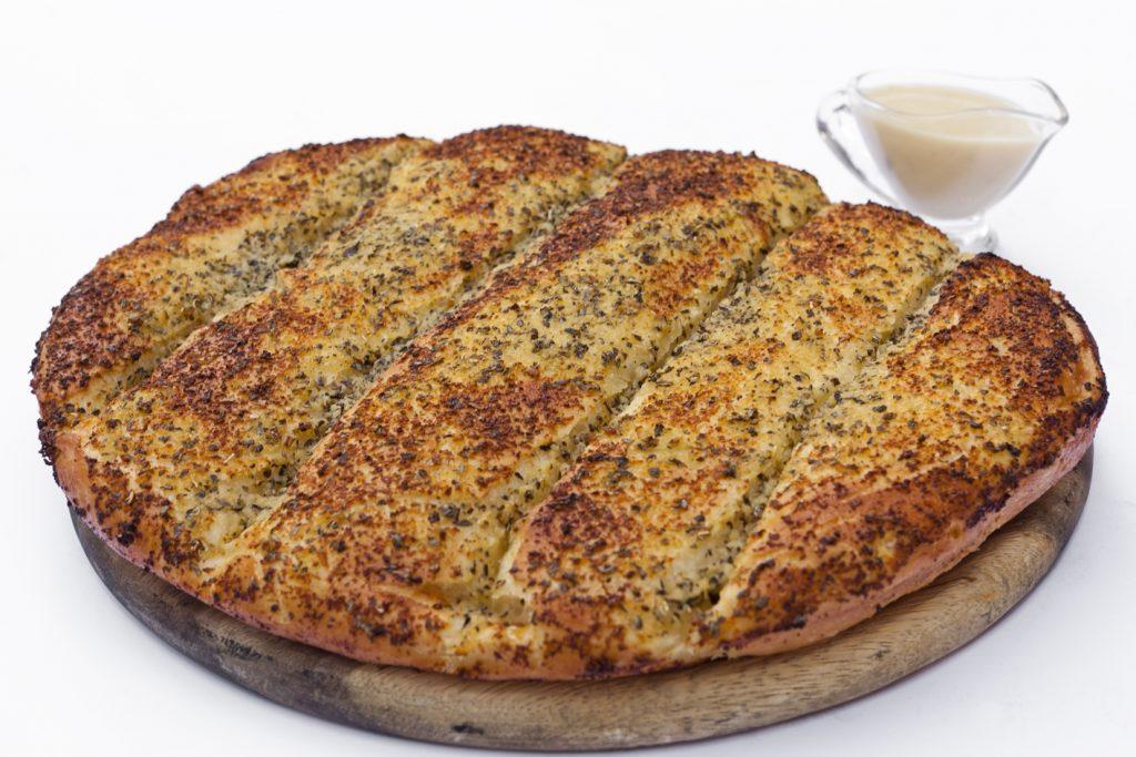 לחם שום מאפה פריך בתבלינים ושום. מוגש עם רוטב שום.